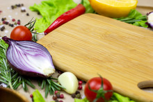 Brown Wooden Cutting Board With Summer Vegetables And Champignon Mushroom On Table Background.