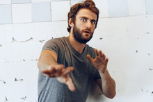 Portrait Of Expressive Young  Bearded Man Scared And Nervous