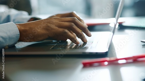 Cuadros en Lienzo Close up hands man african american young uses laptop typing touch work in offic