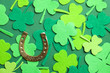 Leinwanddruck Bild - Flat lay composition with clover leaves and horseshoe on green background. St. Patrick's day