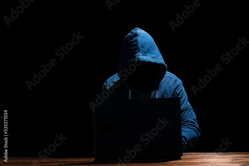 A Hacker with laptop sits at a table and abstract binary code Canvas Print