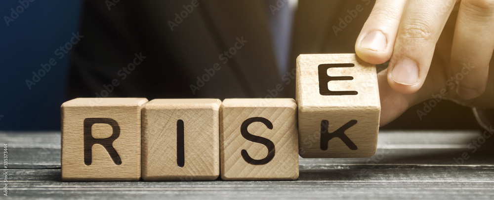 Fototapeta Businessman changes wooden blocks with the words Risk and Rise. Business risk management and growth performance. Risks assessment. Planning strategies and achieving goals.
