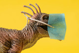 Close up o a plastic dinosaur toy with face mask on yellow background