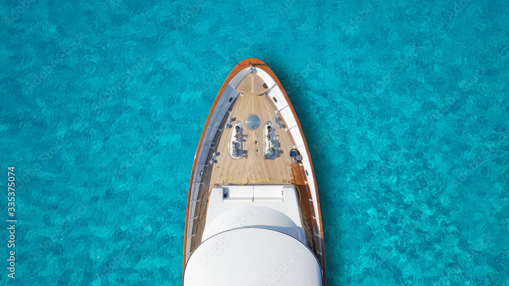 Fototapeta Aerial drone top down photo of luxury exotic yacht nose with wooden deck anchored in paradise turquoise bay