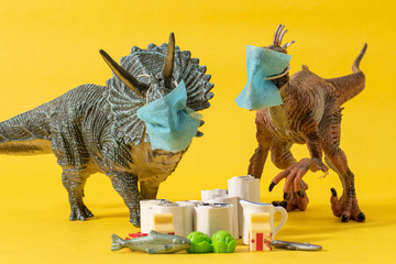 Two plastic dinosaurs with face masks and groceries on yellow background