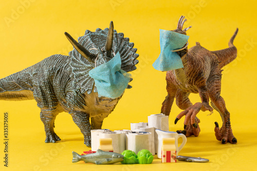 Two plastic dinosaurs with face masks and groceries on yellow background Canvas Print