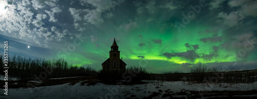 Obraz Silhouette of dilapidated church in small Canadian prairie locations with Northern Lights and stars in the night sky. - fototapety do salonu