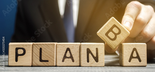 Photo Businessman chooses wooden block with the words Plan A and B