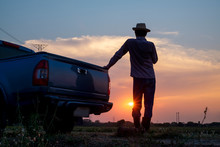 Rear View Of Male Farmer Standing Looking At Farmland At Sunset, Farm Activity Preparation, Traveling By Pickup Truck