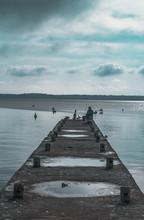 Muelle A La Orilla Del Mar Con Un Pescador Sentado Al Fondo