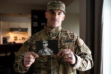 Portrait Proud Male Soldier Holding Photograph Of Father In Uniform