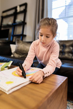 Girl Coloring Rainbow On Notepad In Living Room