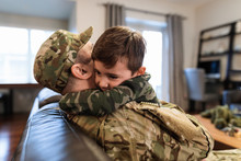 Soldier Father In Camouflage Hugging Son On Sofa