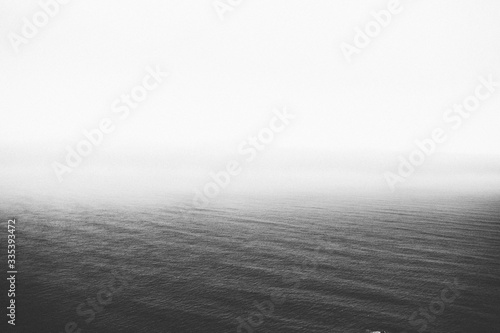 Cuadros en Lienzo Greyscale shot of the calm ocean slowly disappearing at the horizon - perfect fo