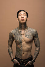 Portrait Of Young Man With Chest Tattoos Looking Up