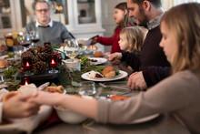 Extended Family Giving Thanks Before Having Christmas Dinner
