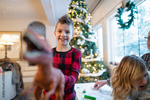Boy playing with new Christmas toy dinosaur gift