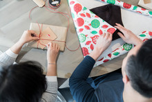 Overhead View Of Couple Wrapping Christmas Gifts On Dining Table At Ho
