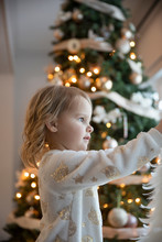 Portrait Of Toddler Girl With Christmas Tree In Background