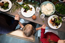 Overhead View Of Family Giving Thanks Before Having Christmas Dinner