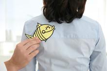 Man Sticking Paper Fish To Col...