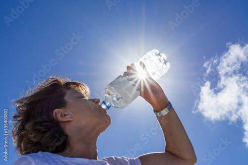 Foto Woman, senior, drinking water in the sunlight, back lit image with sunbeams