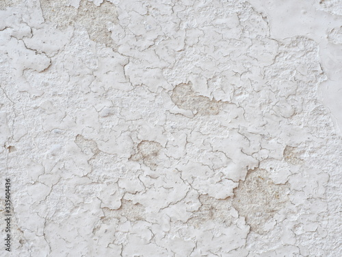 Photo Ditry white old painted wall peeling off cause by low quality paint that has inadequate adhesion and flexibility,Over thinning the paint or spreading it too thin
