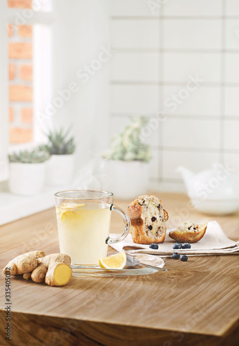 tea with lemon and ginger on a sunny table by the window with a cupcake with blueberries and berries