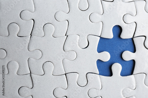 Foto White puzzle with missing piece on blue background, top view