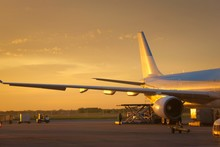 Airport Ground Crew Loading Cargo And Luggage On A Commercial Aircraft At Dawn.