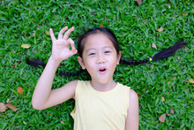 Beautiful Asian Little Child Girl Making Ok Sign Lying On Green Grass Background. Portrait Of Smiling Kid Show Confident Hands Symbol.