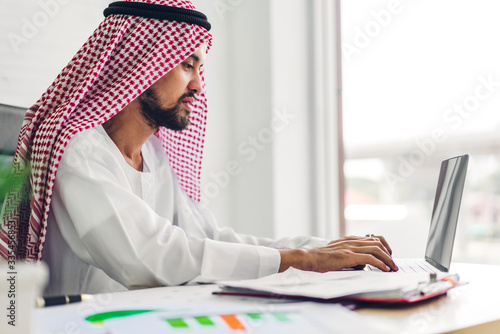 Handsome confident arab businessman working and looking at technology of laptop computer monitor Fototapeta