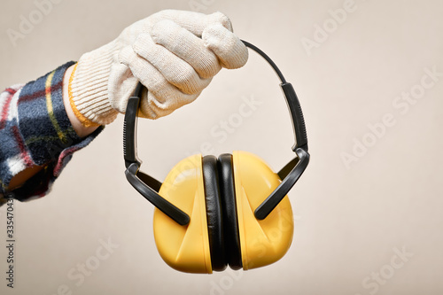 Photo Worker's hand giving protective earphones: hearing protection and labor protecti