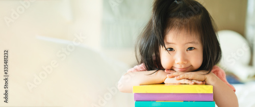 Panoramic portrait of Asian girl toddler smiling put her chin over her hands on the books stack Wallpaper Mural