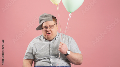 funny happy man, very similar to Winnie the Pooh with balloons, isolated on a pink background, grimaces in the Studio Wallpaper Mural