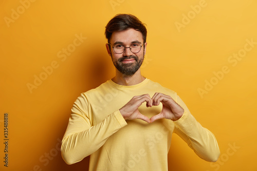 Photo Handsome bearded adult man holds hands in shape of heart, expresses his affection to girlfriend, adores someone, says be my valentine, dressed in near sweater, isolated on yellow background