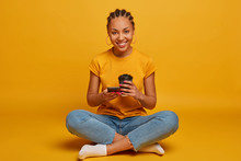 Relaxed Young Afro American Woman Sits Crossed Legs In Lotus Pose, Enjoys Spare Time And Coffee Break, Holds Disposable Paper Cup, Scrolls Internet Social Network, Isolated On Yellow Background
