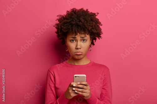 Fényképezés Photo of disappointed dark skinned young woman holds mobile phone, makes unhappy