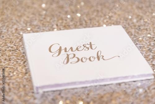Fotografiet Closeup shot of a guest book on a pink sparkling surface