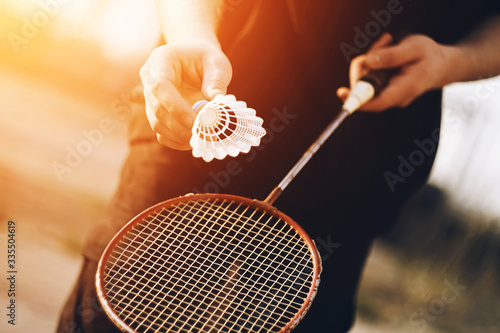 Photo A man is holding a red badminton racket and a white shuttlecock that is going to be thrown into the air on a Sunny, warm day
