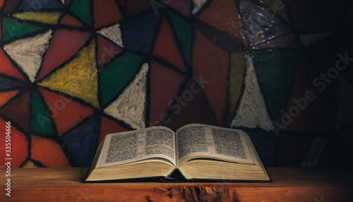 Foto Open Holy Bible on a red wooden table