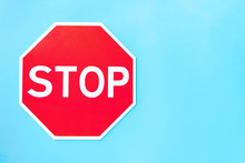 Red Prohibition Road Sign Stop On Left Part Of Blue Background. Prevention Warning Symbol Shows Traffic Ban. Attention Icon Indicates Car No Movement. Caution, Alert, Danger, Risk Concept.