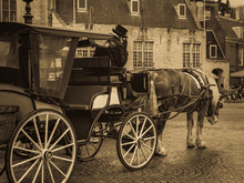 Scene In Dam Square In Amsterdam. Horses With A Classic Carriage And Coachman As A Traditional Transport. Toned Photo, Antique Style.