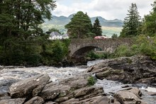The Historical Stone Bridge Of The A827 Road Above The River And Falls Of  Dochart In Killin, Scotland With A Red Car With Motion Blur Effect