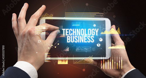 Close-up of hands holding tablet with STARTUP FUNDING inscription, modern business concept