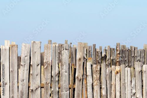 Fototapeta Old rough wooden fence against the blue sky