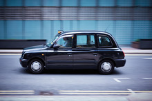 A London Cab Speeds Through A City Landscape