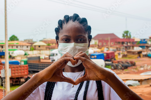 Fototapeta young black beautiful lady wearing a nose mask and giving a love sign with her hand obraz