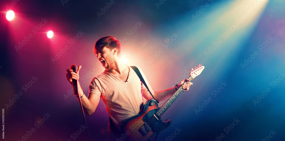 Fototapeta Young male singer performing on a stage and playing the guitar