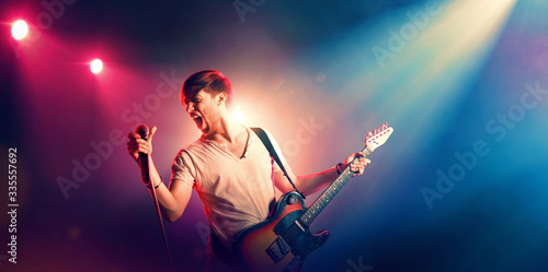 Obraz Young male singer performing on a stage and playing the guitar - fototapety do salonu